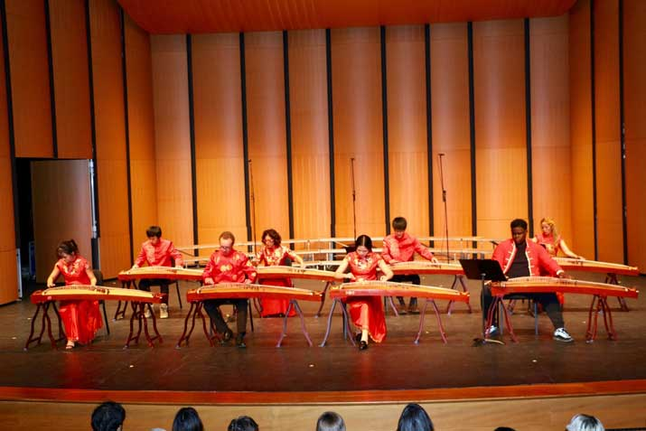 Students playing gunzheng on stage