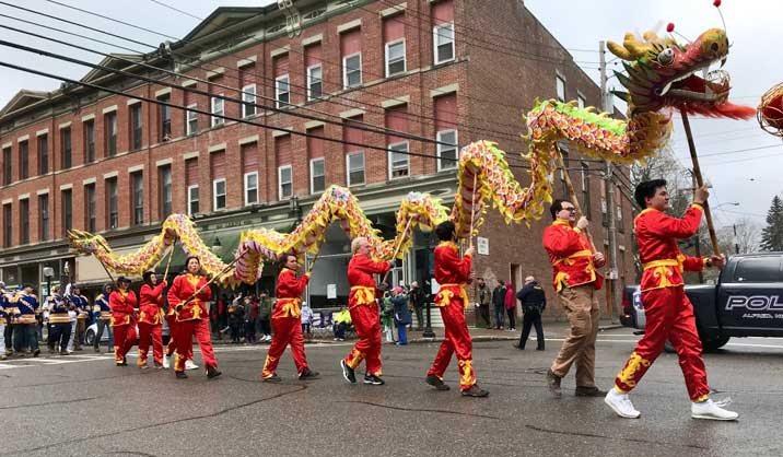 Chinese students carrying dragon down main street of Alfred for the Hotdog Day parade